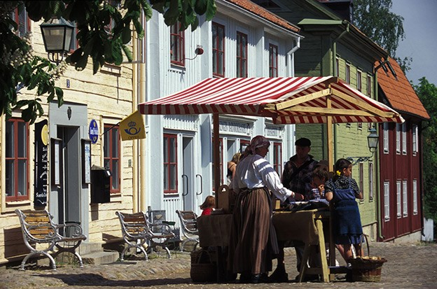 A group of people are assembled around a market stand in a square in Linköping.