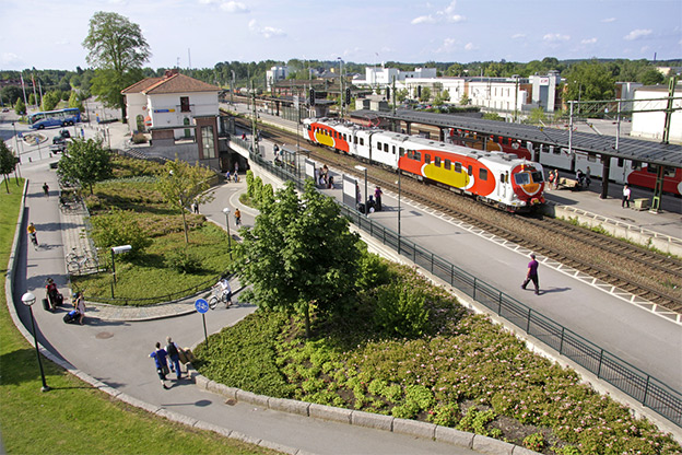 View of Mjölby station. There is a train on the tracks and people waiting on the platform.