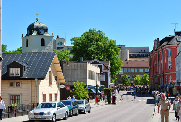 View over buildings in Mjölby. Cars are parked along a road. Groups of people on the pavement.