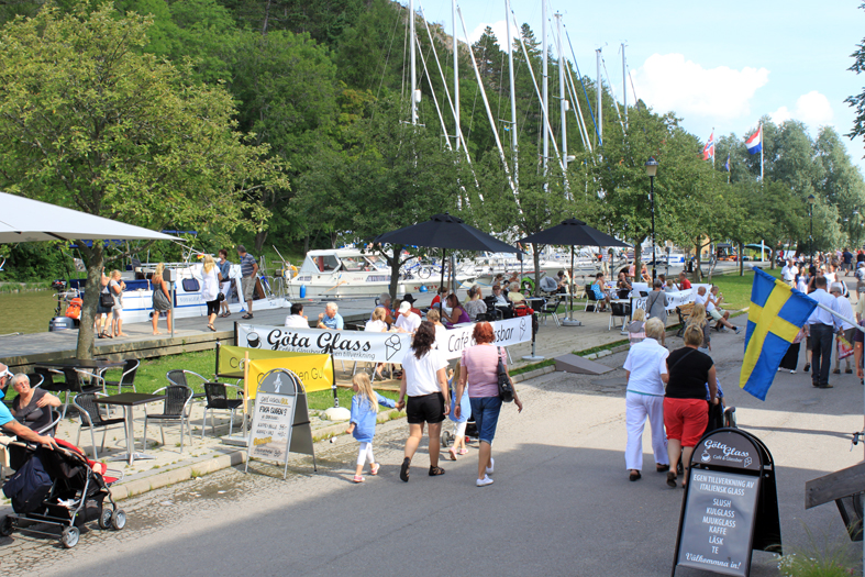 People walking along Göta Canal. Others are eating ice cream at an outdoor café. In the background are boats on the canal.