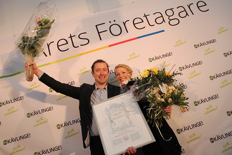 "A man and a woman are standing in front of a wall that says ""Årets Företagare"" (""Business Person of the Year""). They are each holding a bouquet of flowers and a diploma."
