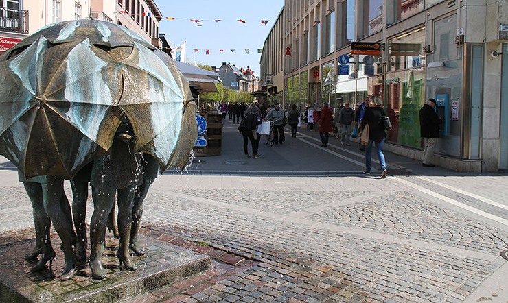 A pedestrian street in Trelleborg. In the foreground is a bronze fountain. The fountain depicts six pairs of legs in heeled shoes, huddled together under several umbrellas.