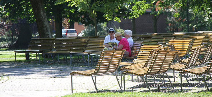 The city park in Trelleborg on a sunny day. A large number of park benches are empty. Three elderly ladies are seated on a park bench talking to each other.