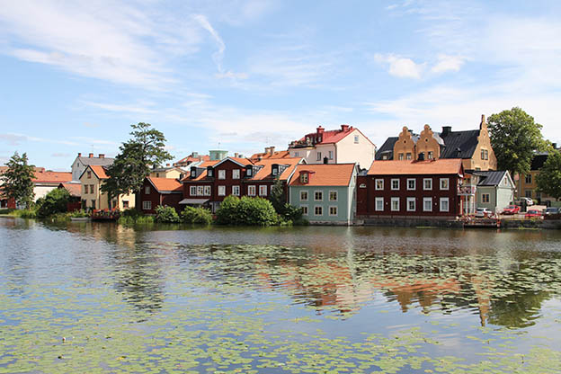 View of houses and buildings in various colours, and of trees and bushes by the water in central Eskilstuna.