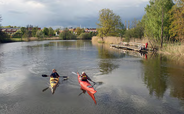 Two people paddling kayaks in a stream, with trees in the surroundings and a town in the background.