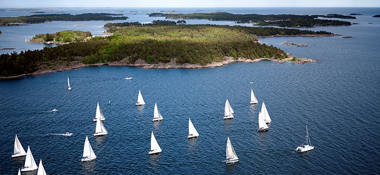 View of an archipelago with many white sailing boats in the water.