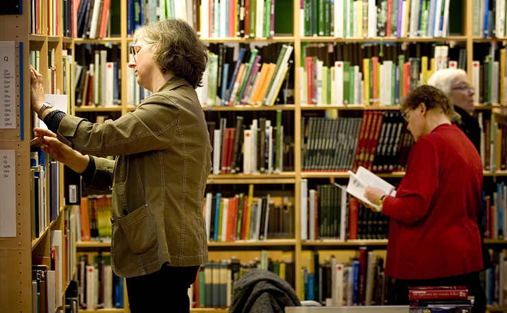 Some ladies are in a library looking for books on shelves full of books on different subjects.