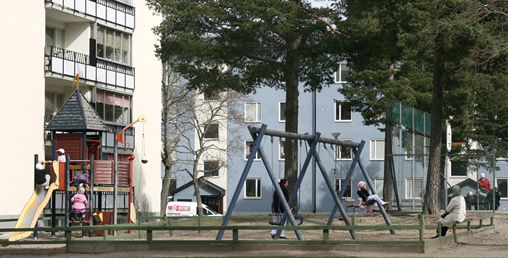 Playground with climbing frames and swings in the foreground, and a blue and white block of flats in the background.