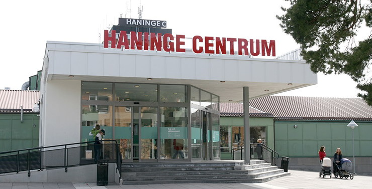A glazed entrance to Haninge Centrum. Some people are entering and a couple of mothers with prams are standing outside the entrance.
