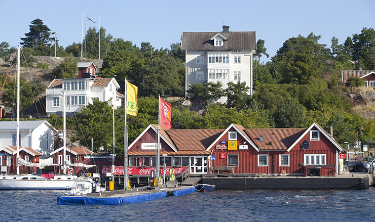 View from the water towards Dalarö. In the foreground is a filling station for boats and a sheltered housing facility. Higher up are some large detached houses.