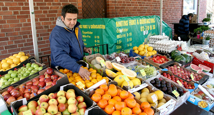 A market stall full of different fruits, run by a self-employed fruit seller.