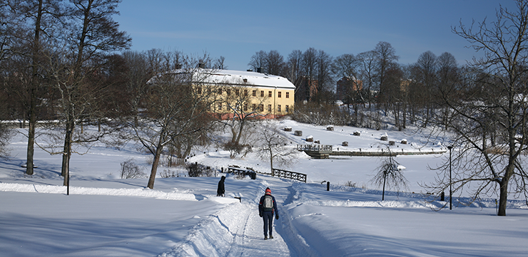 Winter image of a parkland with a big manor and blocks of flats in the background.