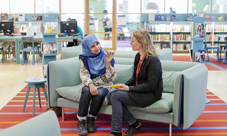 A teenage girl is seated on a blue sofa together with a librarian. In the background is a table with computers visitors can use and bookshelves with books they can borrow.