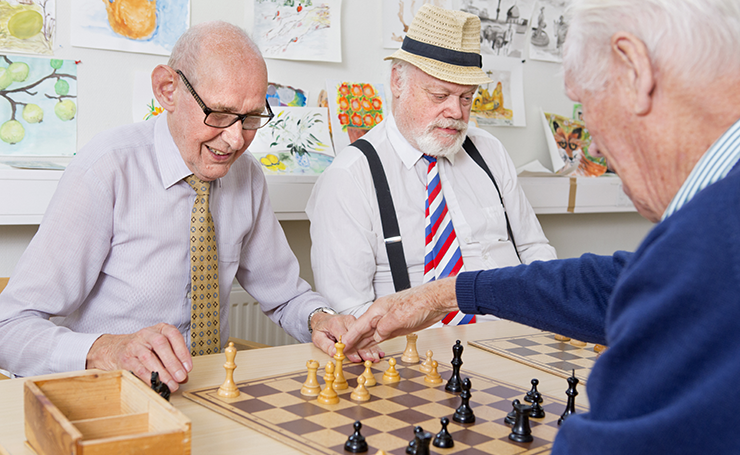 Elderly male members of a chess association playing chess.