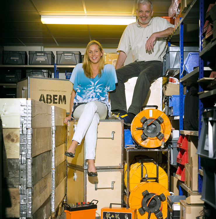 A man and a woman are seated in storage room, surrounded by electronic components.