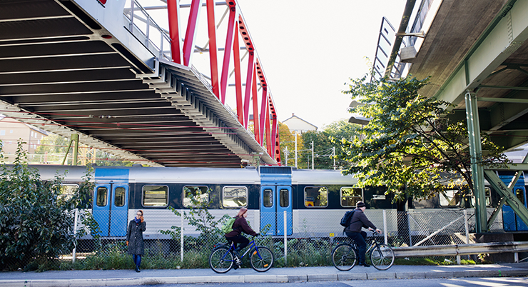 A commuter train station with railway bridge and a viaduct above it. Some people are cycling on the road outside.
