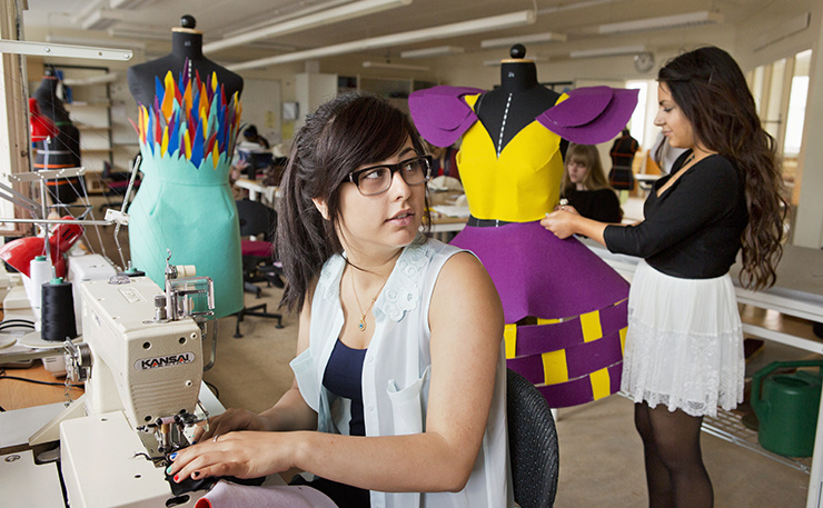 Two young people designing clothes. A girl is sitting at a sewing machine and the other girl is working on a mannequin.
