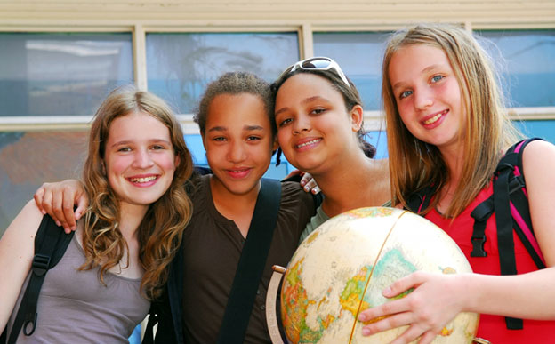Four school pupils holding a terrestrial globe.