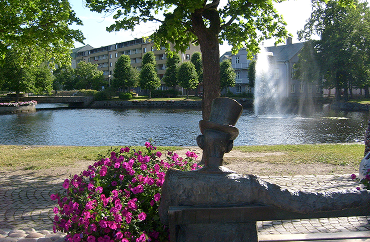 The statue of Nils Ferlin seen from behind, as he looks out over Skillerälven.
