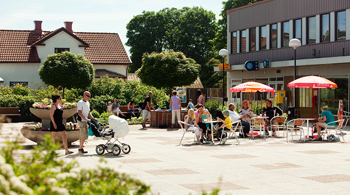 A square with shops in a row. People are seated outside and having coffee in the shade of parasols. A young couple with a pram are walking past.