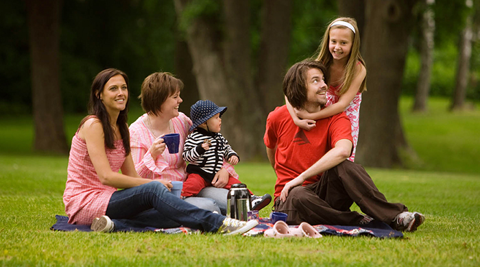 Picnic in a park. A woman with a baby is drinking coffee, and in front of her is a younger woman. Next to them is a young man, and a girl is messing around with him.