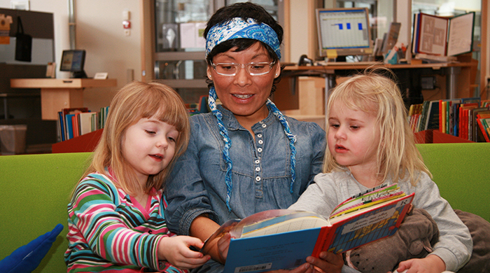 Seated on a green sofa in the library, a woman is reading a storybook to two girls aged around five.