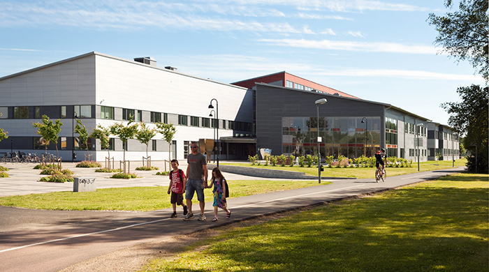 A father is walking on the path outside a modern school building with his son and daughter. In the distance a boy can be seen cycling in the opposite direction.