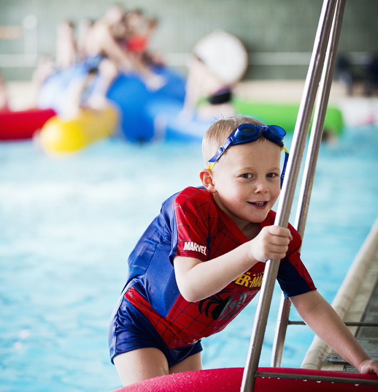 A boy in a Spiderman suit with swimming armbands is climbing the ladder out of the pool. In the background other children are playing with inflatable toys.
