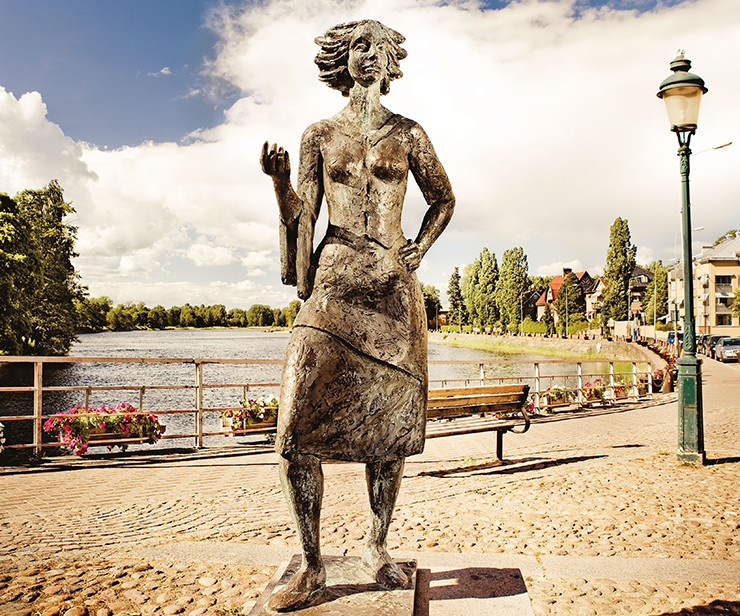 "The statue ""Sola i Karlstad"" (""The Sun in Karlstad"") in bright sunshine, with Klarälven in the background."