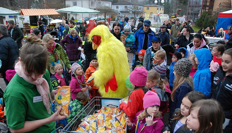 Party in the centre in April. There are market stalls and lots of children being given bags of sweets by a person in a bird suit.