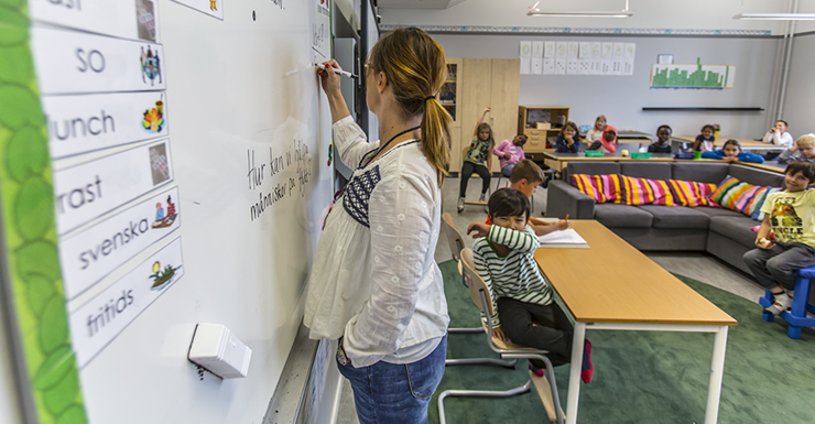 A teacher is writing on a whiteboard in a classroom. Pupils are seated at their desks and looking at the board.