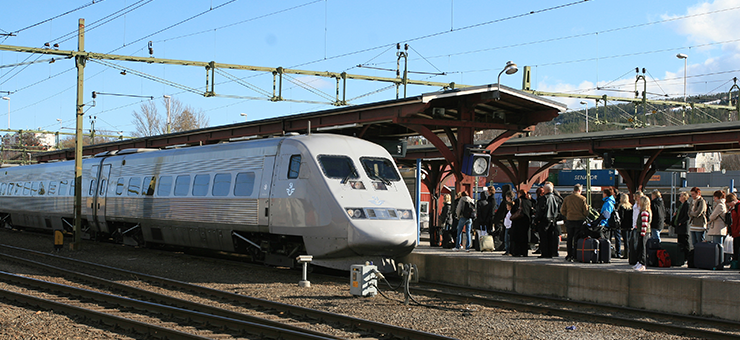 A silver-coloured train has stopped at a station. A group of people are waiting on the platform.