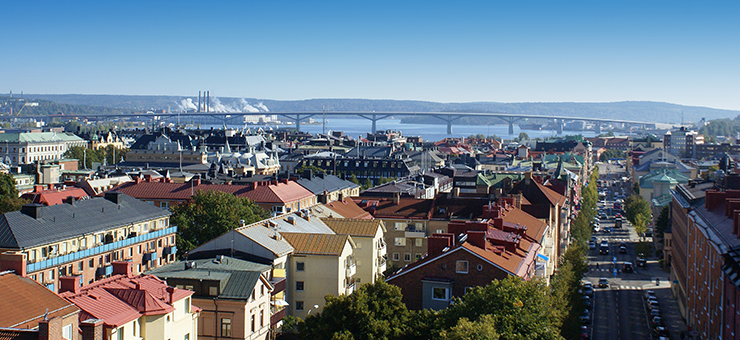 View over Sundsvall. In the background the Sundsvall Bridge extends across a blue sea.