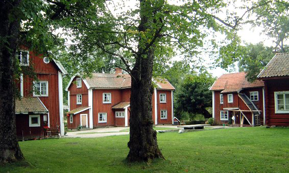 Brategården in Norberg municipality. Three red houses with white-painted corners in a verdant setting.