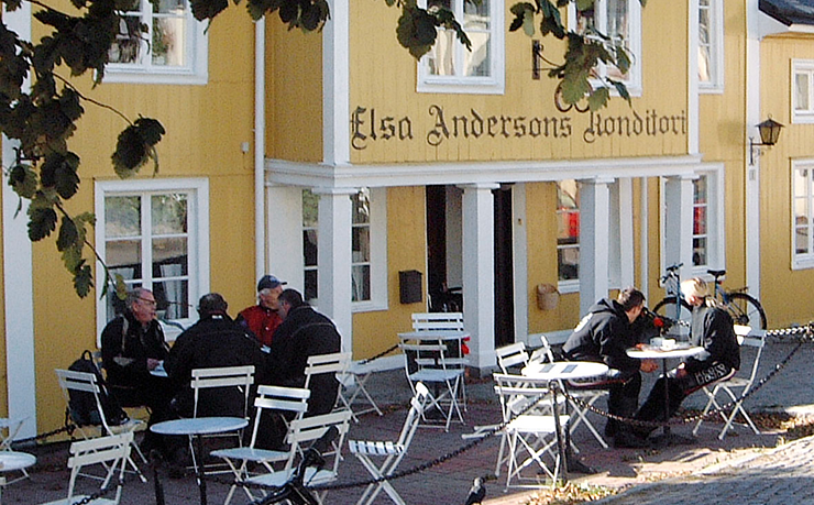 Elsa Andersons Konditori (patisserie). A yellow wooden house with white trim. People are having coffee and cakes at the tables outside the patisserie.