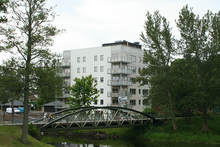 A block of flats with a park in the foreground.