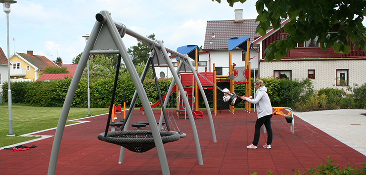 A playground with swings and a child swinging.