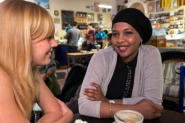 Two women meeting over coffee through the Refugee Guide project.