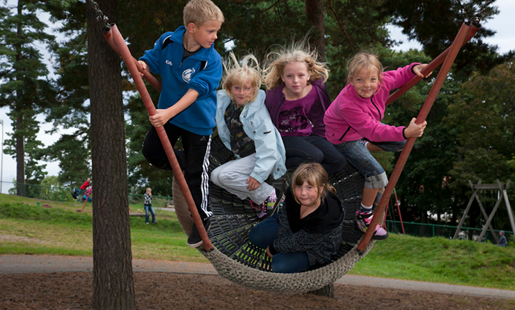 Primary school pupils playing on a swing.