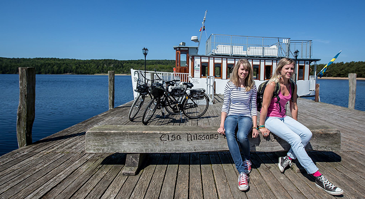 Two girls seated on the jetty waiting for a boat ride on Lake Lyngnern.