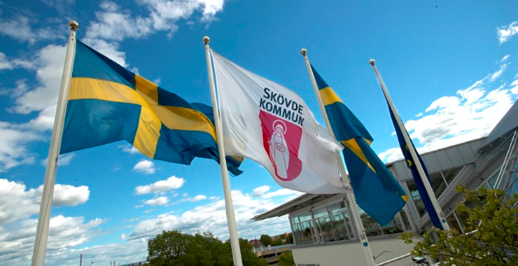 Swedish flags flying around a flag with Skövde's coat of arms.
