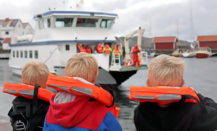 Children wearing life jackets wait for the ferry, which can be seen arriving in the background.