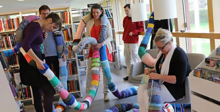 Several people helping to knit a long snake for the library's cosy corner.