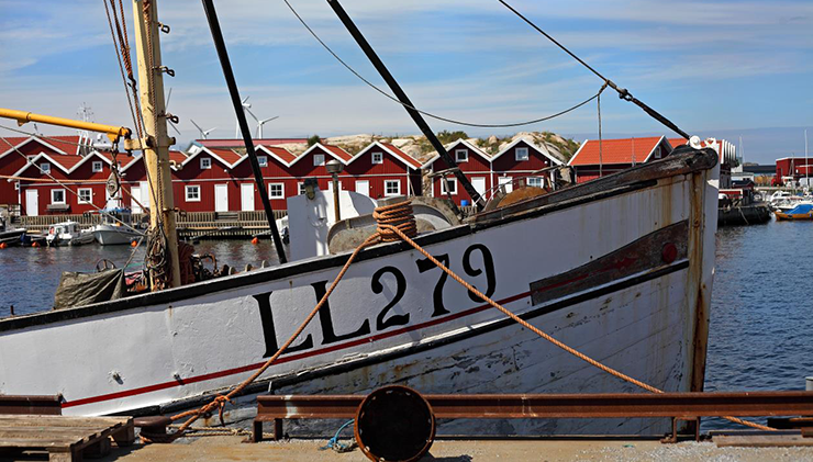 A fishing boat with fishing sheds in the background.