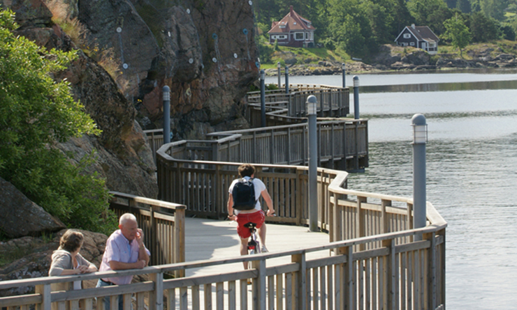 People strolling and cycling along the waterfront promenade.